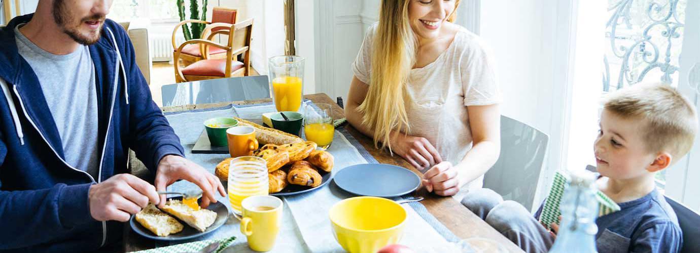 Een gezin van drie zit 's ochtends aan tafel te ontbijten