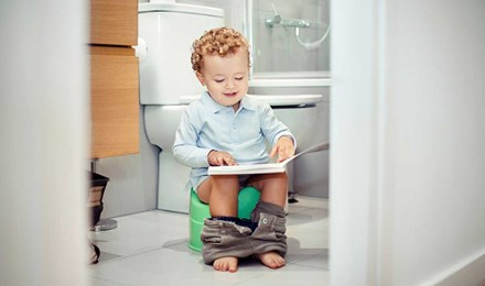 Een kleine jongen zit op een potje te kijken naar een boek op zijn schoot
