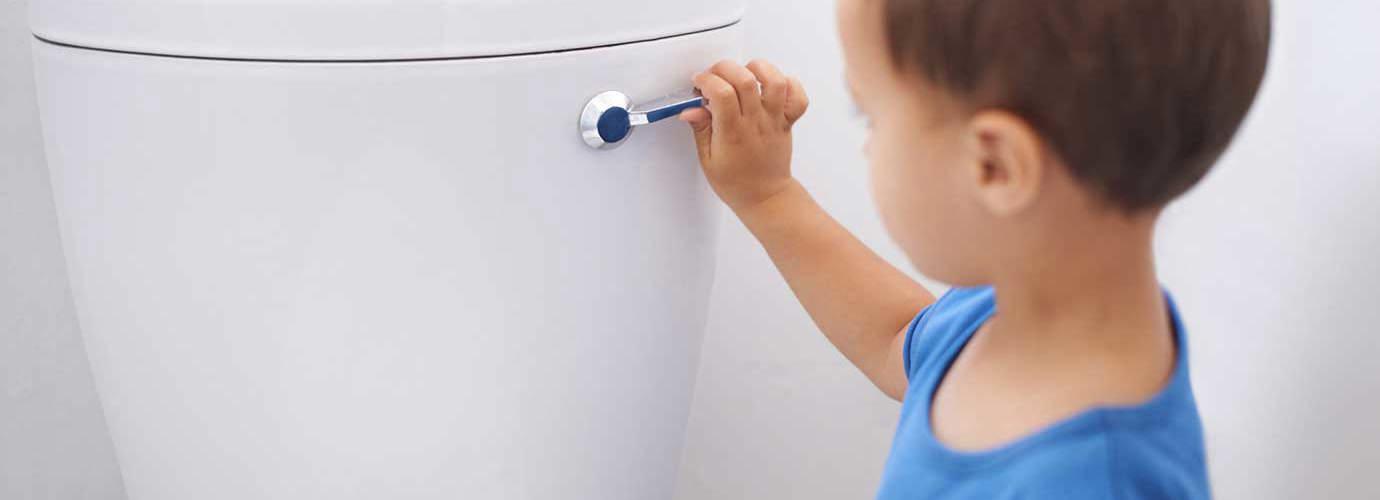 Een kleine jongen spoelt het toilet door