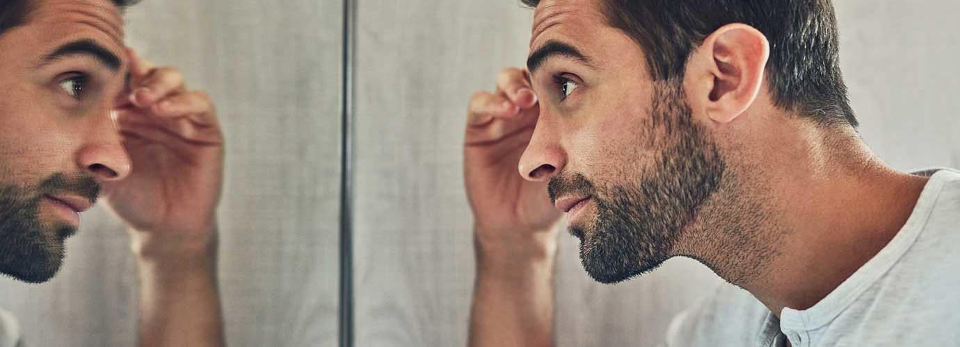 Man kijkt naar zichzelf in de spiegel